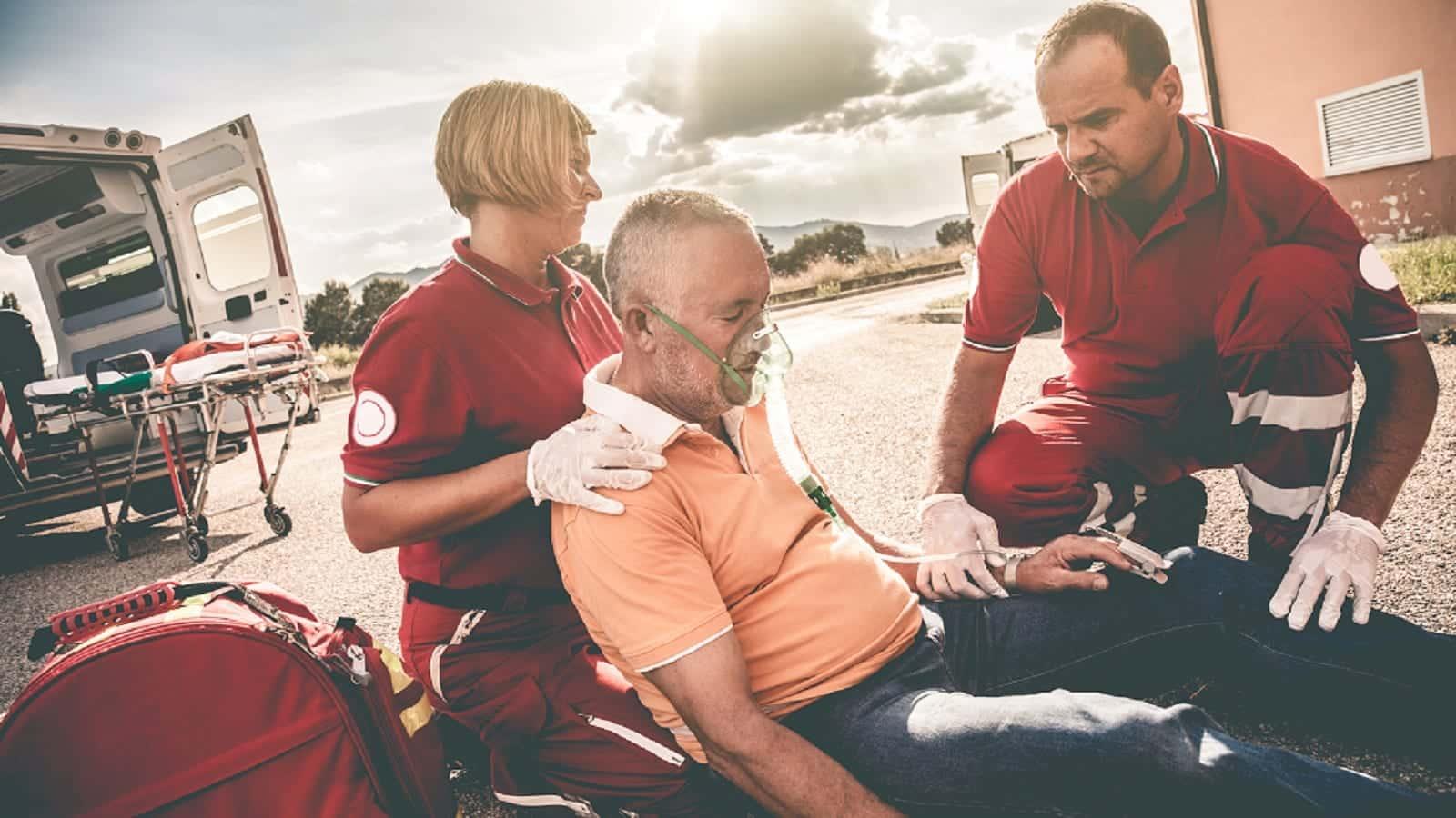 Paramedics With Elderly Man Stock Photo