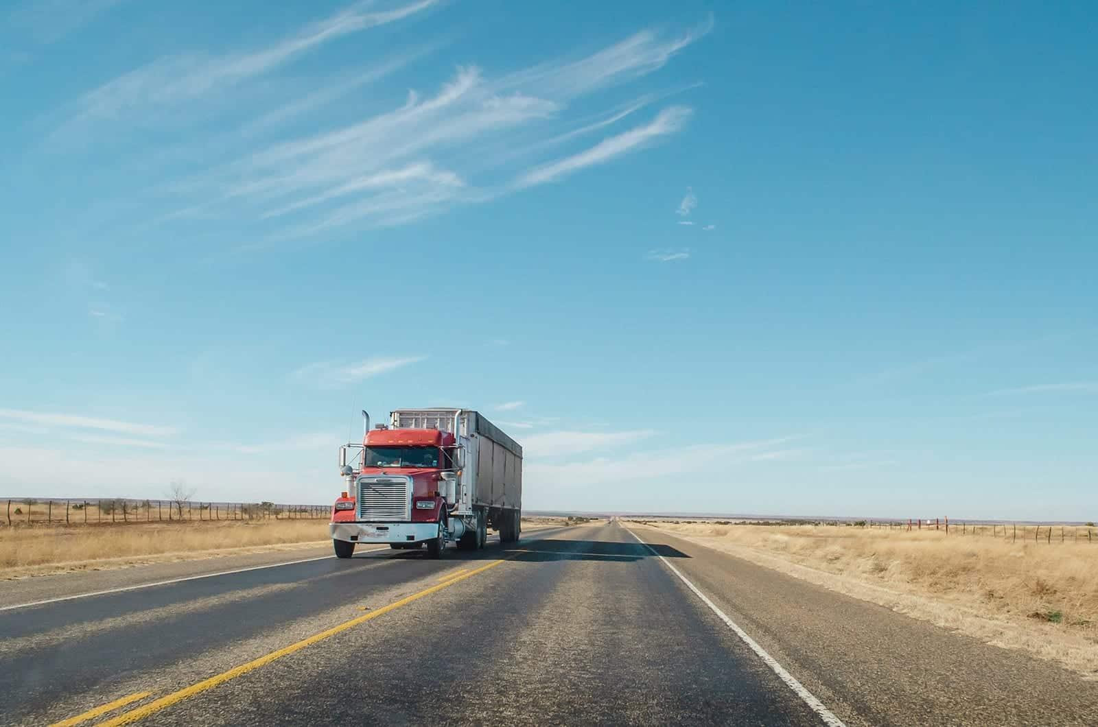Tractor trailer truck driving down desert highway