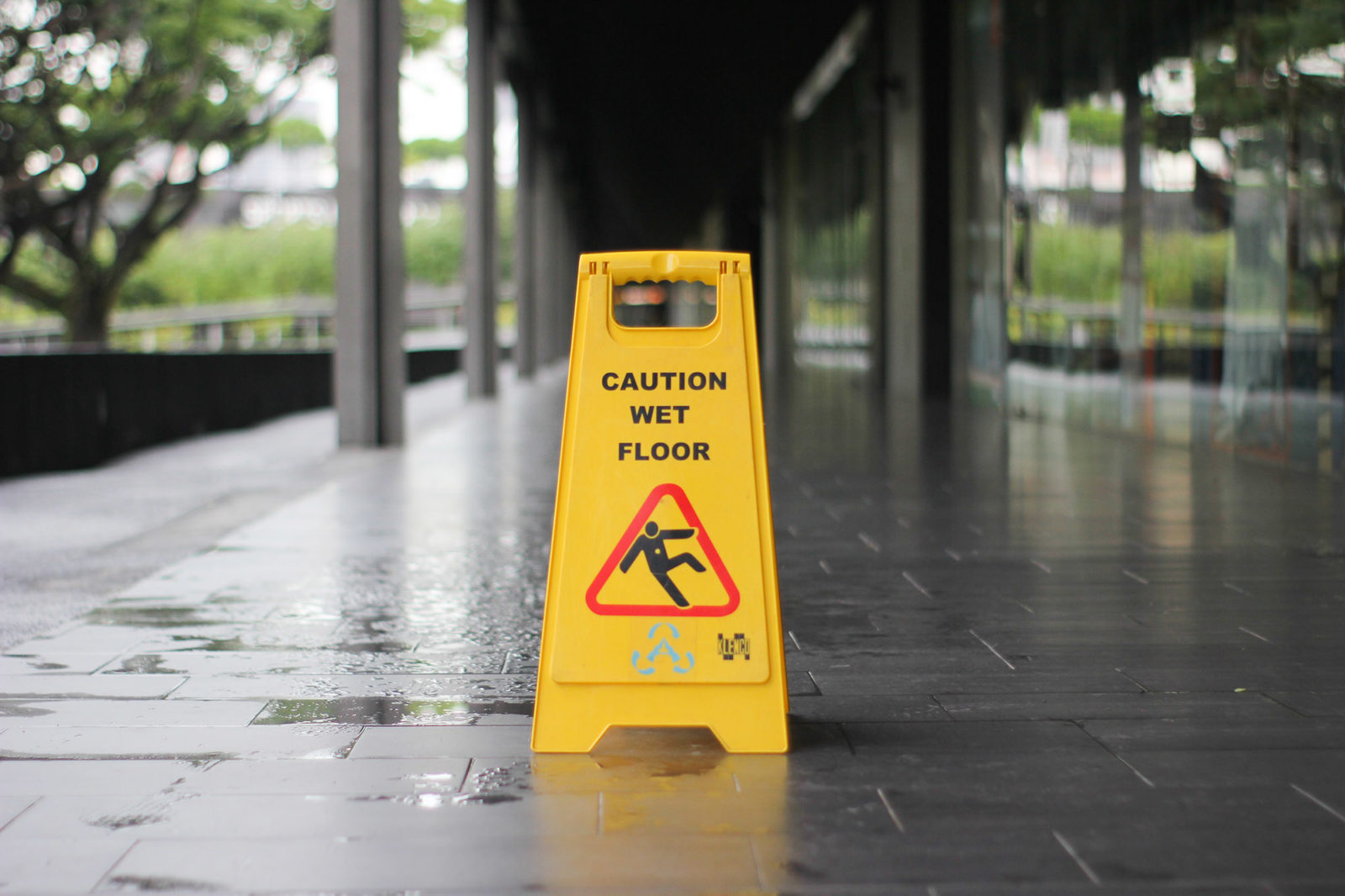 Wet floor sign in the middle of a puddle of water